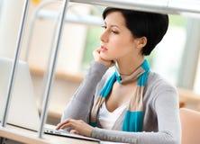 Donna che lavora al computer portatile d'argento Immagine Stock