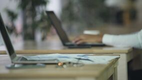 Donna che lavora al computer portatile, al telefono ed alle carte sullo scrittorio, atmosfera all'ufficio della società video d archivio