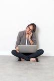 Donna che lavora al suo computer portatile, parlante sul telefono che si siede sul pavimento Fotografie Stock Libere da Diritti
