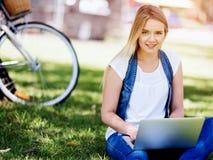 Donna che lavora all'aperto in un prato con il computer portatile Immagine Stock Libera da Diritti