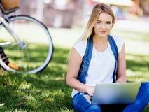 Donna che lavora all'aperto in un prato con il computer portatile Immagini Stock