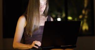 Donna che lavora alla notte al computer portatile archivi video