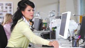 Donna che lavora allo scrittorio in ufficio creativo occupato stock footage