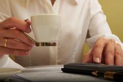 Donna che lavora con i documenti con un caffè Immagine Stock