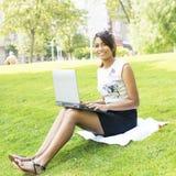 Donna che lavora con il computer che si siede nel parco. Fotografie Stock Libere da Diritti