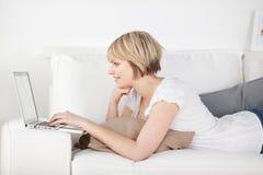 Donna che lavora con un computer portatile sul sofà Fotografie Stock