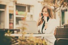 Donna che lavora con un telefono e un computer portatile Immagini Stock Libere da Diritti