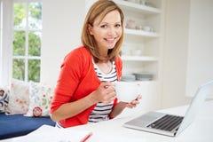 Donna che lavora dalla casa facendo uso del computer portatile in cucina Fotografie Stock