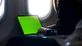 Donna che lavora dentro l'aeroplano sul suo computer portatile personale archivi video