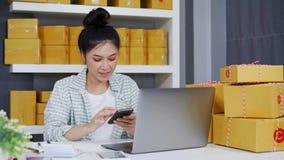 Donna che lavora e che controlla ordine del prodotto con il suo ufficio dello smartphone a casa stock footage