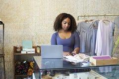 Donna che lavora nel negozio di vestiti che controlla prezzo da pagare, vista frontale fotografia stock libera da diritti