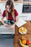 Donna che lavora nella cucina con il computer portatile Lavoro a distanza domestico Fotografia Stock Libera da Diritti
