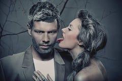 Donna che lecca uomo \ 'la guancica di s Immagini Stock