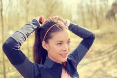 Donna che lega capelli in coda di cavallo che si prepara per il funzionamento Fotografia Stock Libera da Diritti