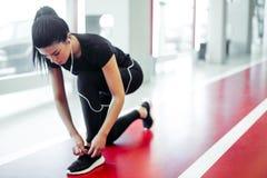Donna che lega i laccetti alla palestra di forma fisica prima dell'correre sulla pista corrente fotografie stock