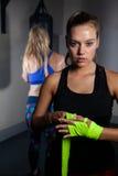 Donna che lega l'involucro della mano a disposizione nello studio di forma fisica Immagini Stock