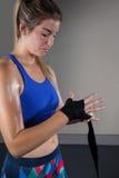 Donna che lega l'involucro della mano a disposizione nello studio di forma fisica Immagini Stock Libere da Diritti