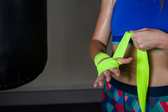 Donna che lega l'involucro della mano a disposizione nello studio di forma fisica Fotografia Stock