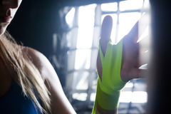 Donna che lega l'involucro della mano a disposizione nello studio di forma fisica Fotografia Stock Libera da Diritti