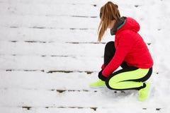 Donna che lega le scarpe di sport durante l'inverno Immagine Stock Libera da Diritti