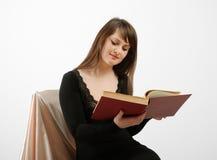 Donna che legge il grande libro isolato sul bianco Immagini Stock