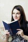 Donna, che legge il libro che si siede sul sofà Fotografie Stock