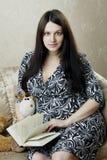 Donna, che legge il libro che si siede sul sofà Immagini Stock Libere da Diritti