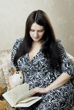 Donna, che legge il libro che si siede sul sofà Fotografie Stock Libere da Diritti