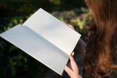 Donna che legge libro in bianco in giardino Fotografia Stock Libera da Diritti