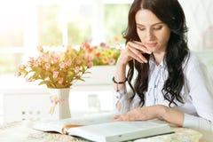 Donna che legge libro interessante Fotografie Stock