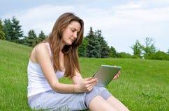 Donna che legge lo schermo del suo ridurre in pani Fotografie Stock