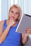 Donna che legge un calcolatore del ridurre in pani Fotografie Stock