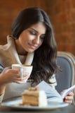 Donna che legge un libro al caffè Fotografie Stock Libere da Diritti