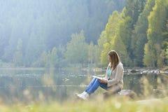 Donna che legge un libro all'aperto Fotografia Stock