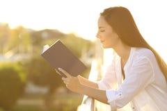 Donna che legge un libro in un balcone al tramonto Fotografia Stock