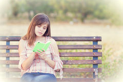 Donna che legge un libro che si siede sul banco Fotografie Stock