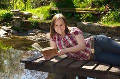 Donna che legge un libro dallo stagno Immagine Stock