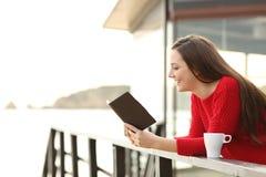 Donna che legge un libro elettronico in vacanza immagine stock libera da diritti