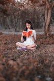Donna che legge un libro nella sosta Fotografia Stock