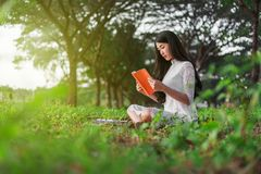 Donna che legge un libro nella sosta Immagini Stock Libere da Diritti