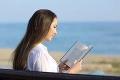 Donna che legge un libro su un banco sulla spiaggia Fotografia Stock Libera da Diritti