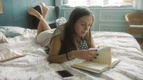Donna che legge un libro su un letto stock footage