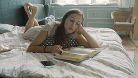 Donna che legge un libro su un letto archivi video