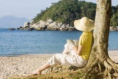 Donna che legge un libro su una spiaggia Fotografie Stock Libere da Diritti