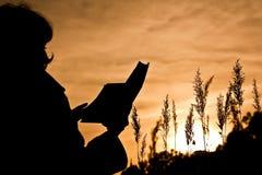 Donna che legge un libro sulla natura Fotografia Stock