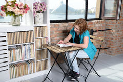 Donna che legge un libro sulla sedia vicino alla finestra Fotografie Stock Libere da Diritti