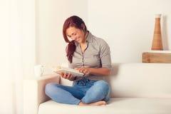 Donna che legge un libro sullo strato a casa Immagini Stock