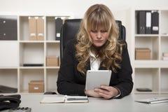 Donna che legge un messaggio sulla sua compressa sul lavoro Immagine Stock Libera da Diritti