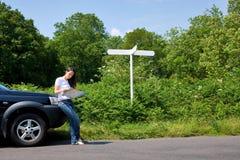 Donna che legge un programma dal bordo della strada con i sig in bianco Immagini Stock Libere da Diritti