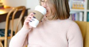 Donna che legge un romanzo mentre mangiando caffè video d archivio